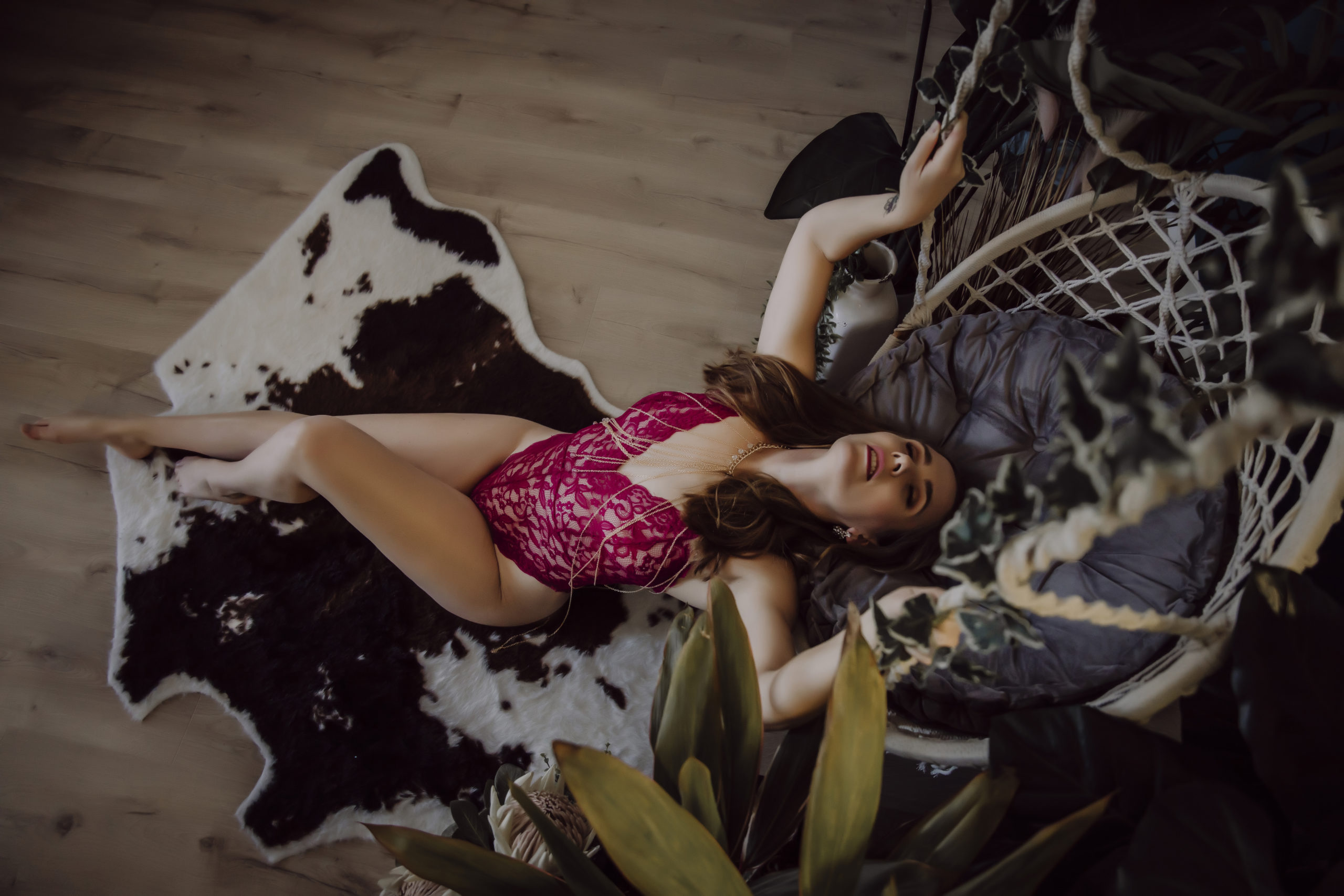 Brisbane Boudoir Photography client posing in red lingerie on a cowhide rug